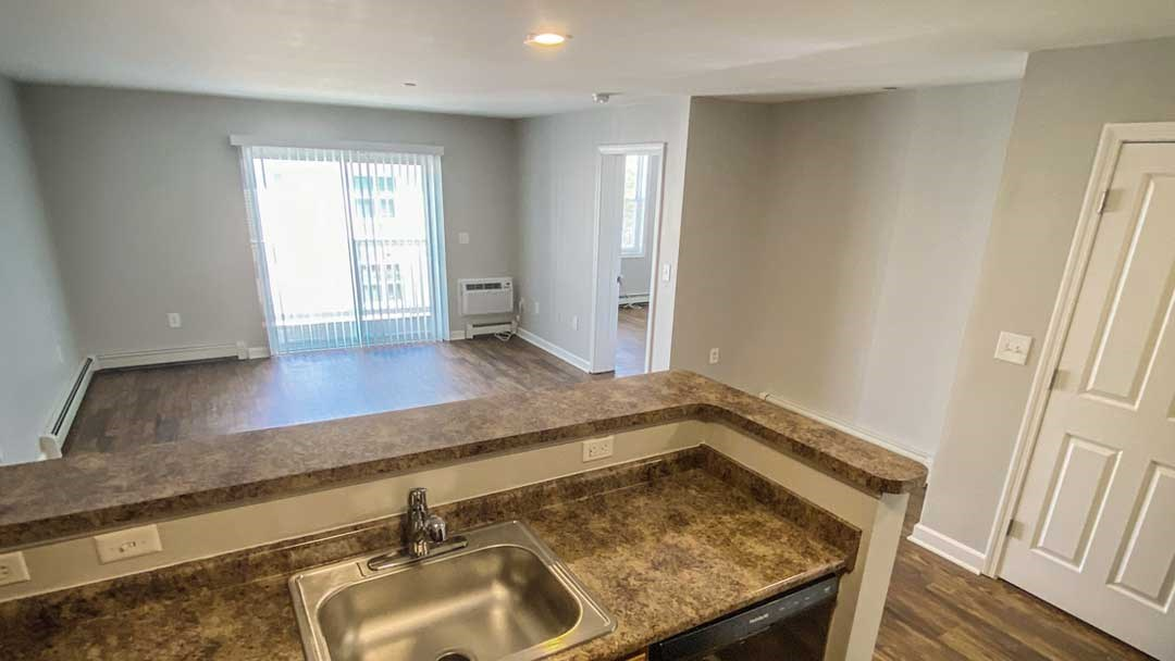 View from the kitchen shows granite style counters, plank flooring, sliding door to balcony.