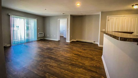 View of the living space from the hallway shows beautiful flooring and large sliding glass door to balcony.