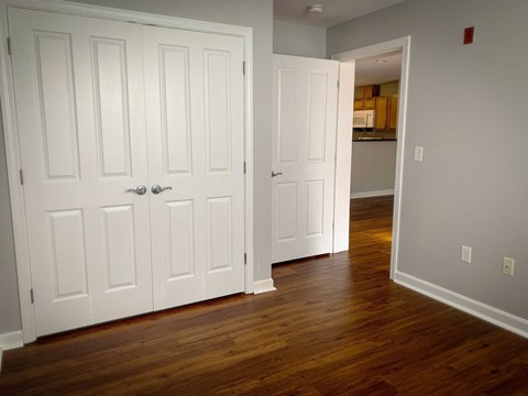 Bright bedroom featuring hardwood flooring and large closets.