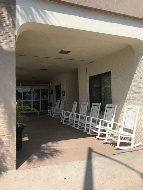 bank of rocking chairs under covered front entrance