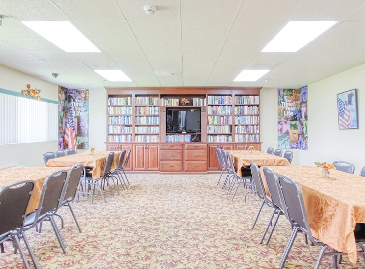 large community room with tables, chairs, TV, and many shelves of books