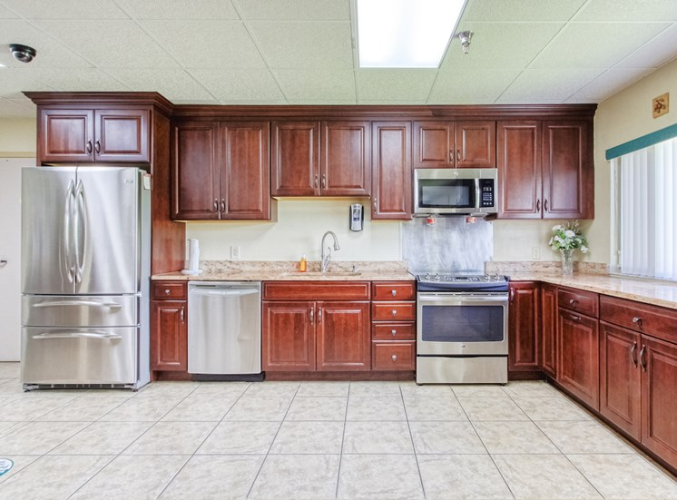 community kitchen with stainless steel appliances, tile floors, and ample cabinetry