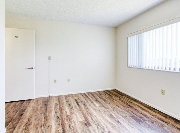 bedroom with large window and hardwood-style flooring