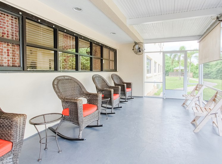 screened-in patio with rockers, chairs, and sun screens