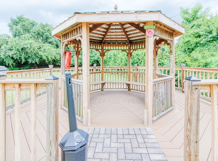 Gazebo with seating surrounded by trees