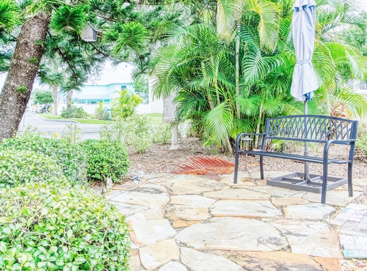 outside patio with metal bench and umbrella surrounded by lush landscaping