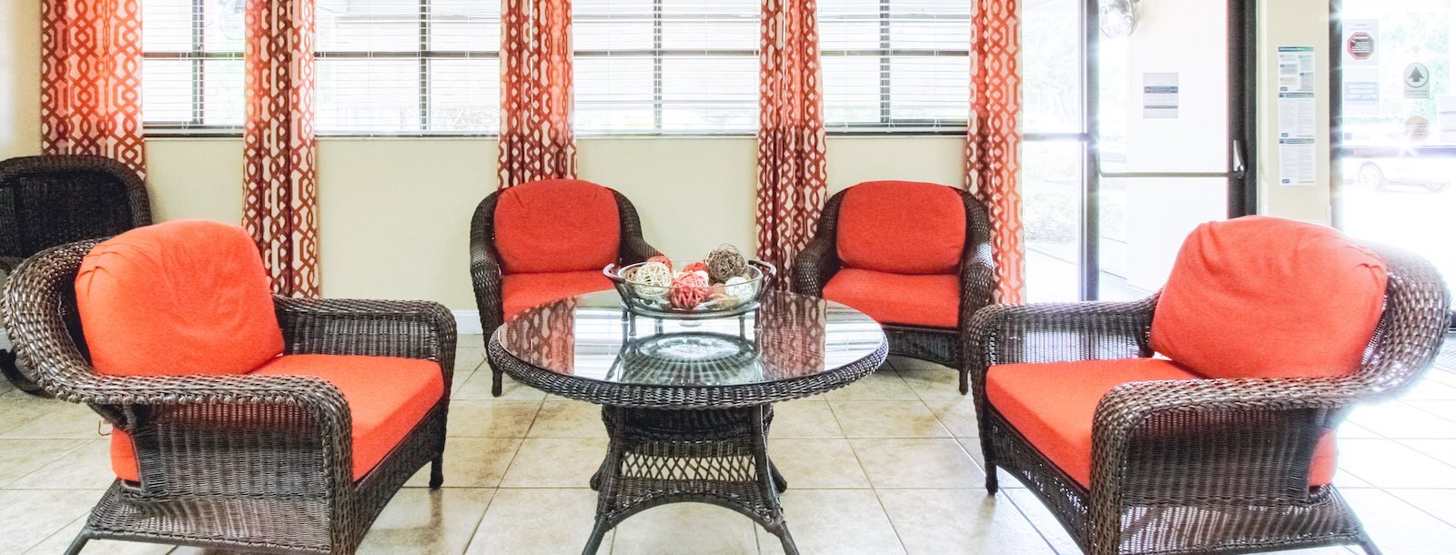 comfortable lobby sitting area with wicker chairs and couch with thick cushions