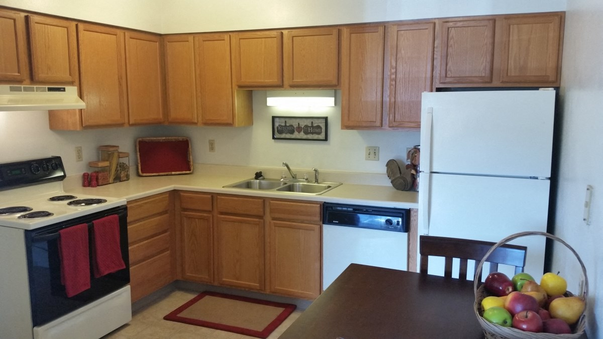 Seville Kitchen 1 Kitchen with electric range, dishwasher, and refrigerator at Seville Apartments in Iowa City, IA