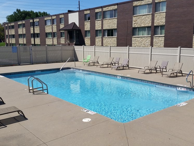 Swimming pool with furniture at Seville Apartments in Iowa City, IA