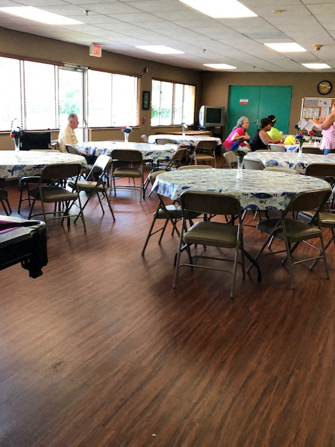 tables and chairs beside large windows in community room at Deedco Gardens