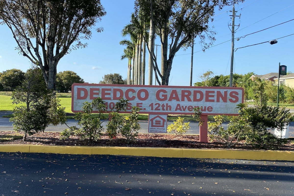 Deedco Gardens Signage with lush trees and bushes