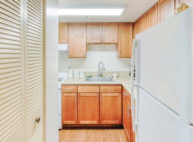 kitchen with white appliances, wood cabinets, and pantry doors