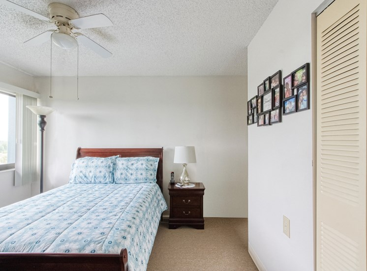 bedroom with large window, ceiling fan, closet, and model furnishings