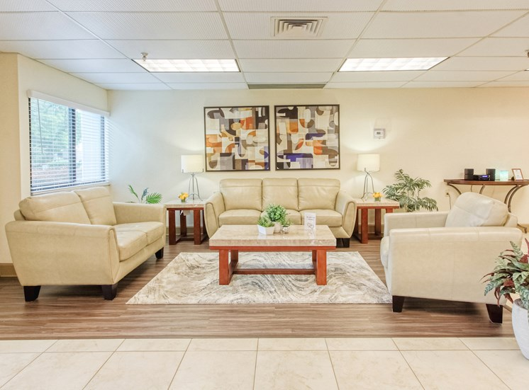large lobby with comfortable sofas, modern flooring, large windows, and overhead lighting