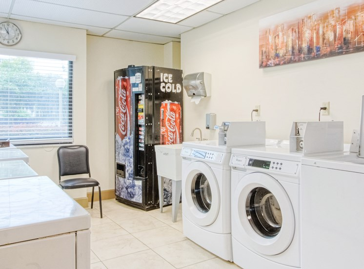 washers and dryers in laundry center with drink machine and wash sink