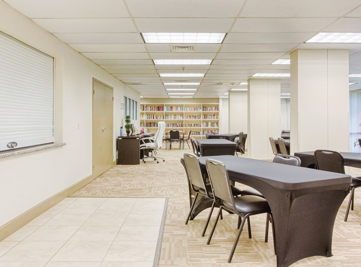 large community room with tables and chairs by computer station & library