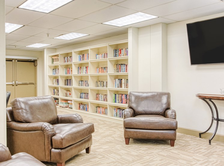 library with leather reading chairs, shelves of books, and TV
