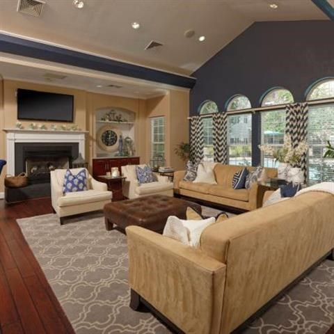luxurious clubhouse with indoor seating area, television, and fireplace