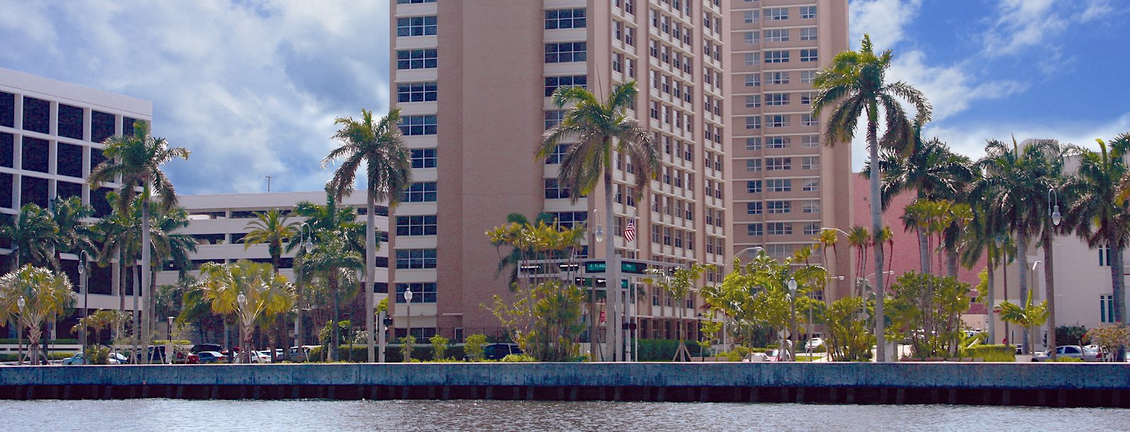 apartment tower surrounded by lush palms in front of the water