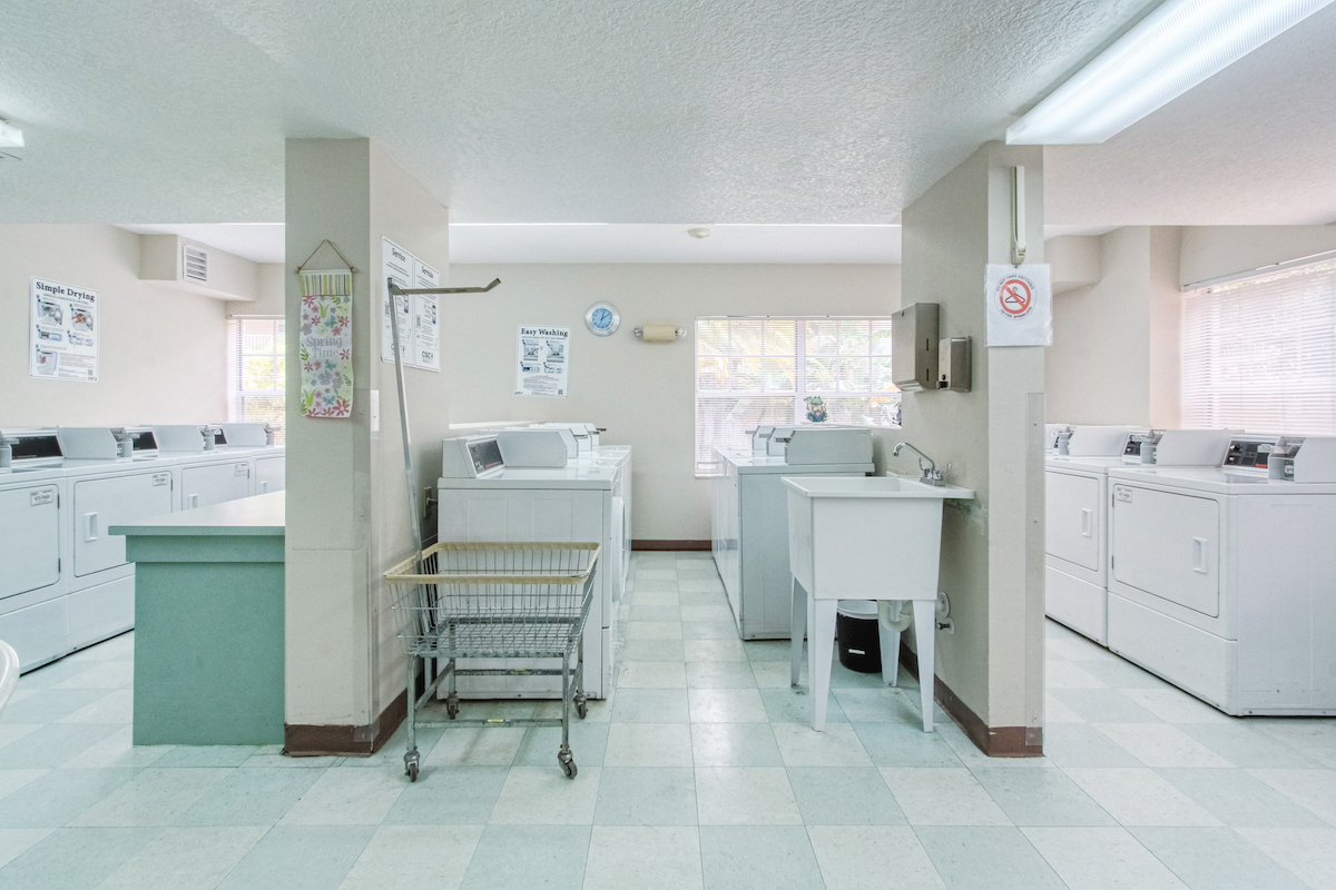 large laundry center with washers, dryers, carts, folding tables, and sinks