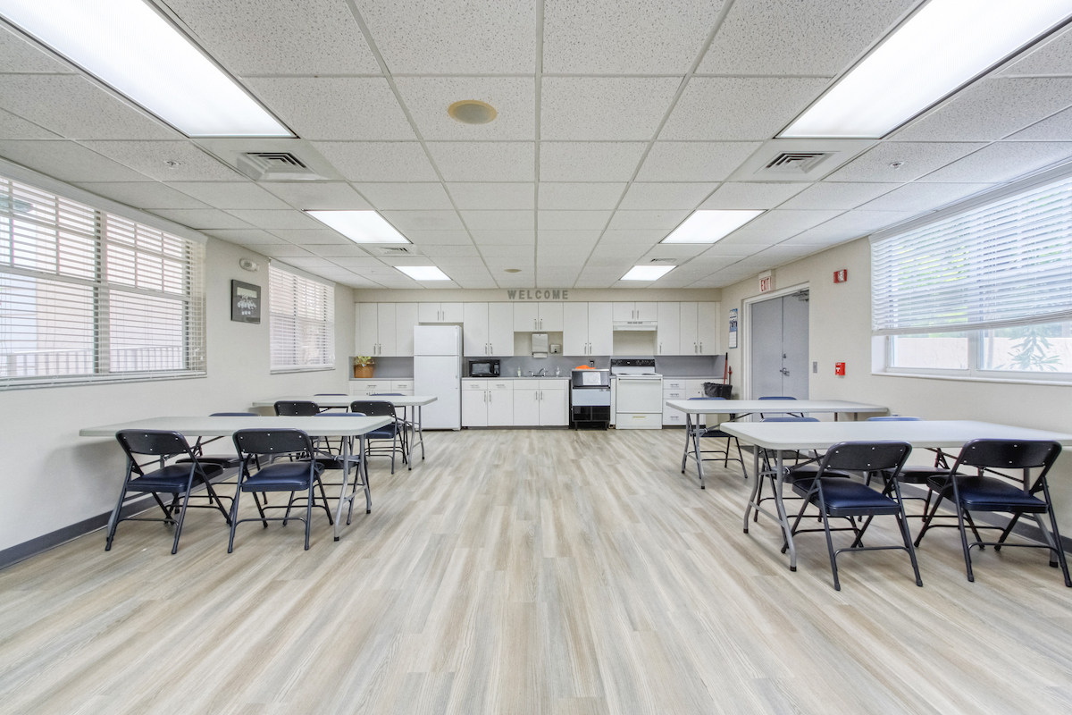 community room with kitchen and tables and chairs for residents