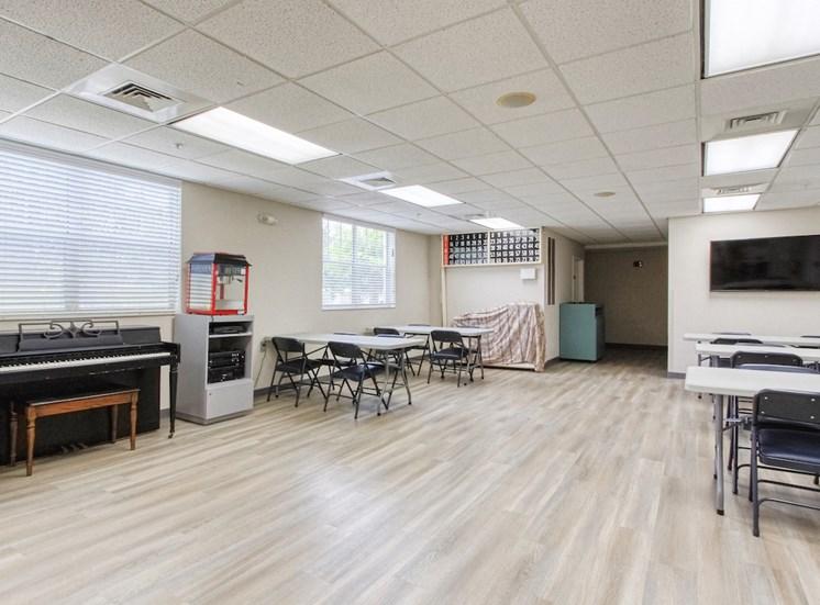 community room with piano, popcorn machine, and bingo wall