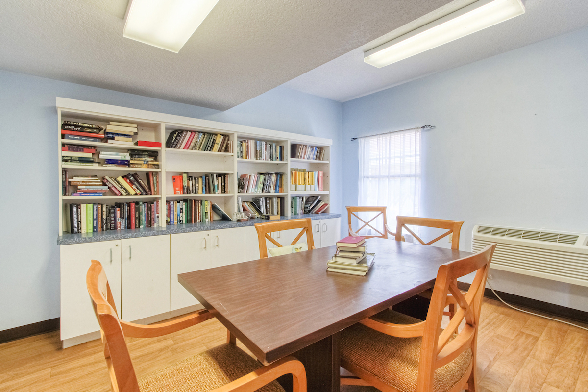 library reading room with many books and large table with chairs