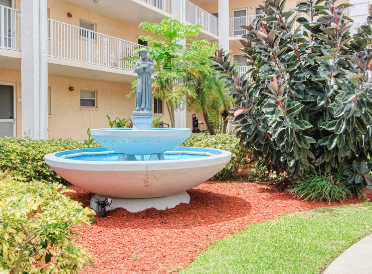 Beautiful sparkling fountain in lushly landscaped courtyard