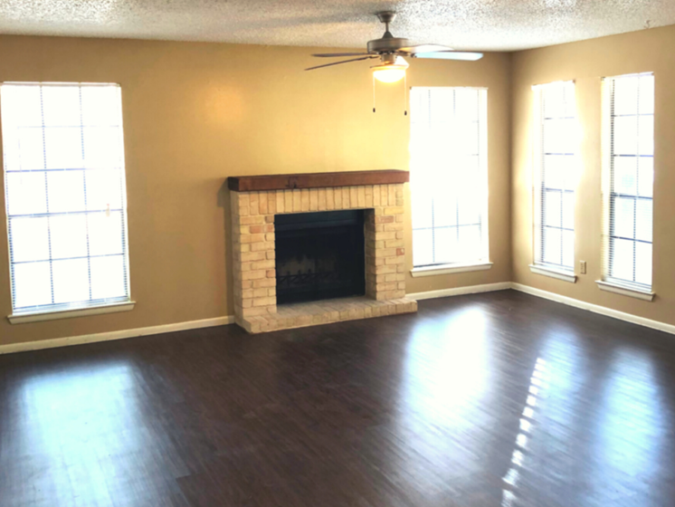 open living room with dark hardwood floors, a fireplace, and 4 wall length windows