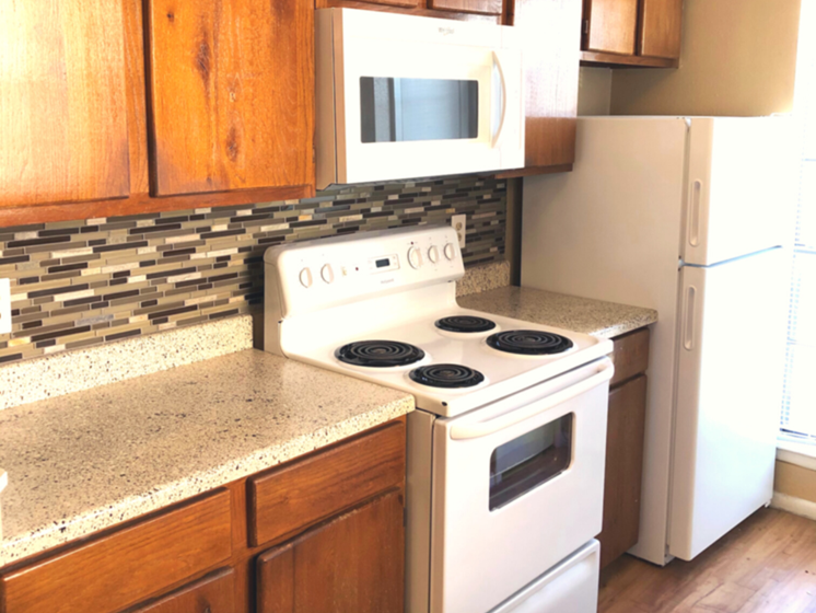 Sunlit kitchen with multicolored tile back splash, white appliances, and light cherrywood cabinets