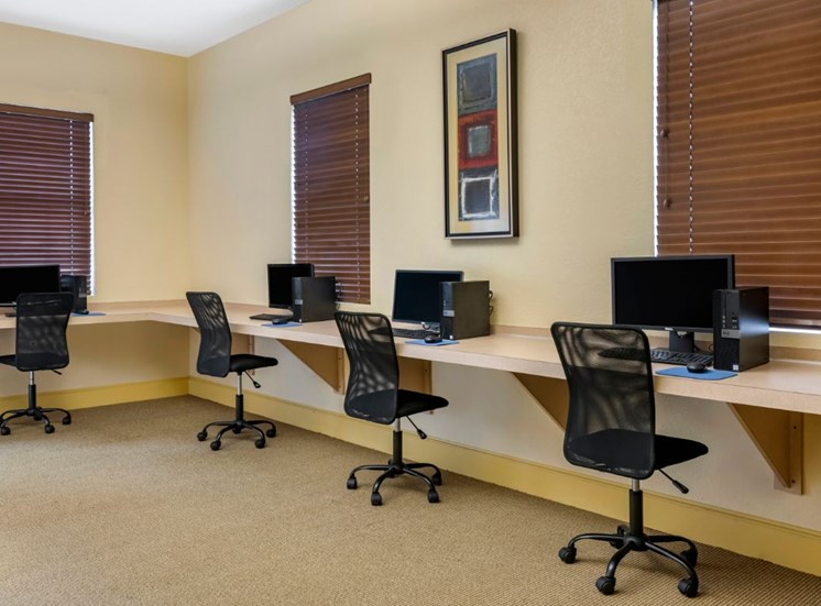 Clubhouse business center equipped with computers, chairs, and large windows for natural lighting