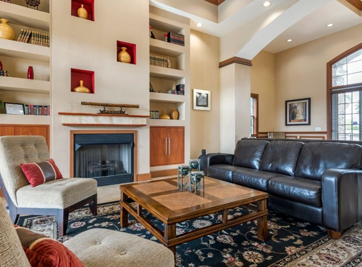 Clubhouse lounge with couches, chairs, coffee table, rug, fire place, and book shelves