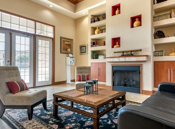 Clubhouse lounge with fire place, built-in book shelves, rug, couch, chairs, coffee table, and large windows for natural lighting