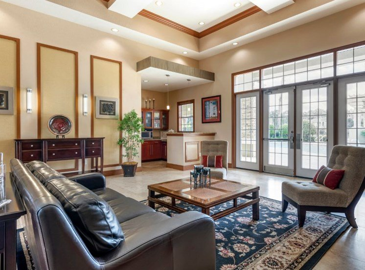 Clubhouse lounge with couch, chair, coffee table, high ceilings, and large windows for natural lighting