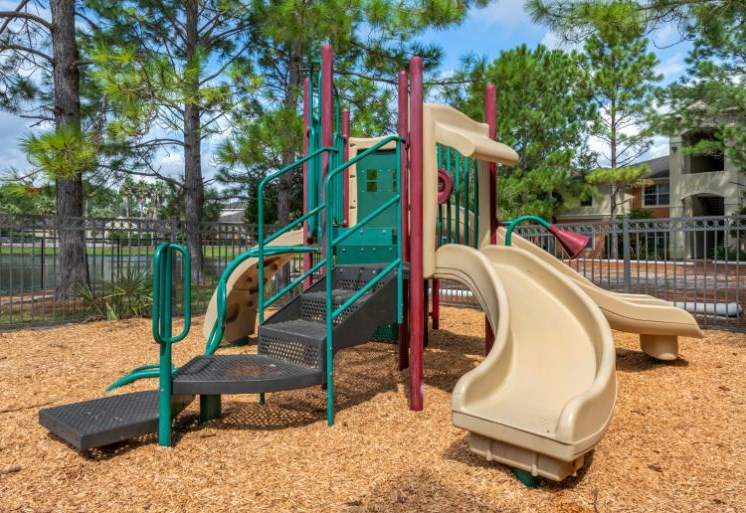 Outdoor playground with seesaw, bench seating, surrounded by native landscaping