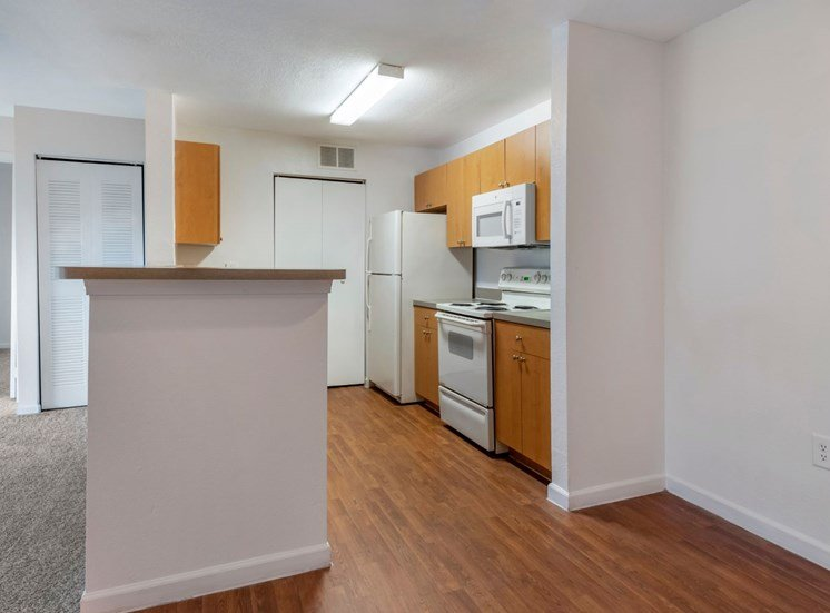 Dining room with hardwood style flooring and fully equipped kitchen with white appliancces