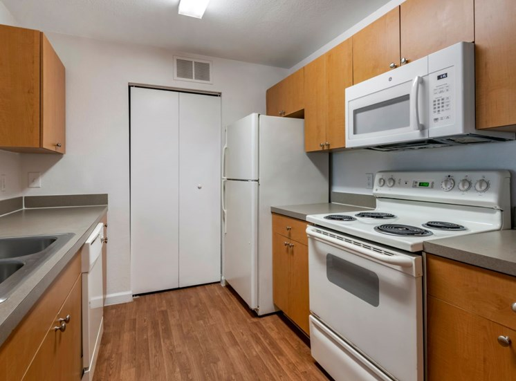 Fully equipped kitchen with hardwood style flooring, white appliances, and double basin sink