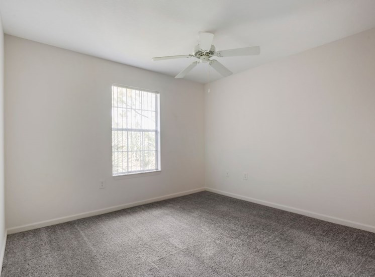 Spacious bedroom with carpet flooring, multi speed ceiling fan, and large window for natural lighting