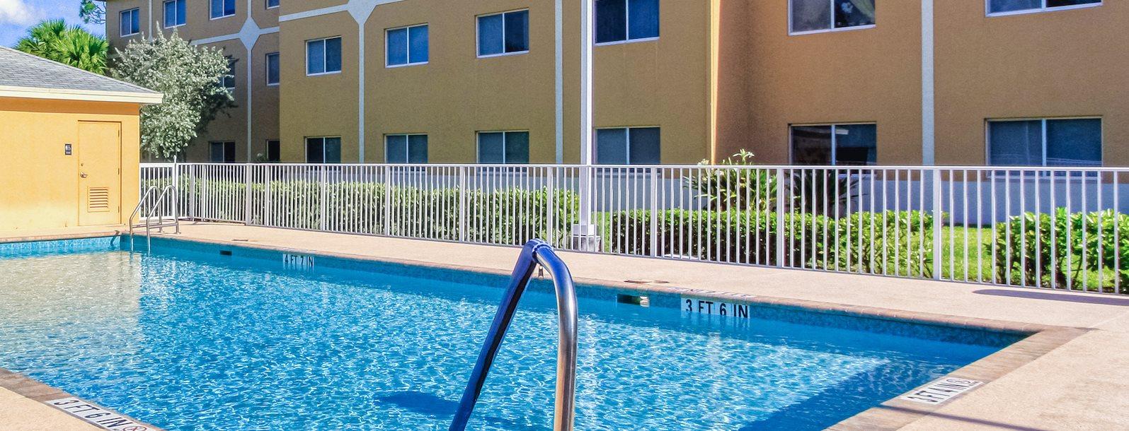 Sparkling pool at Villa Seton beside apartment buildings