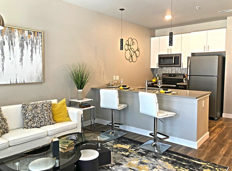 Open concept kitchen and living room space, equipped with stainless steel appliances and bar top seating.