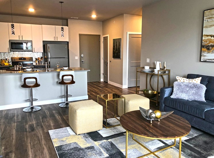 Spacious, open concept living room and kitchen, equipped with stainless steel appliances and bar top seating.