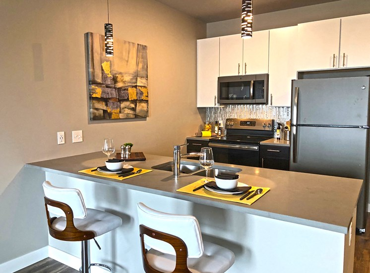 Apartment kitchen equipped with stainless steel appliances and bar top seating