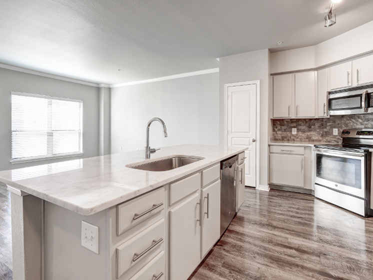 Kitchen with island, white cabinets, gray wood-style flooring, and gray backsplash