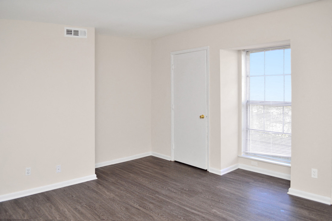 large window and plank flooring in apartment bedroom