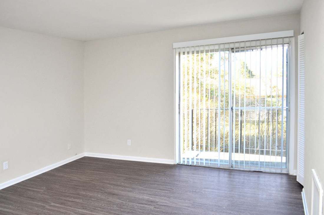 sliding glass door with vertical blinds leading to deck