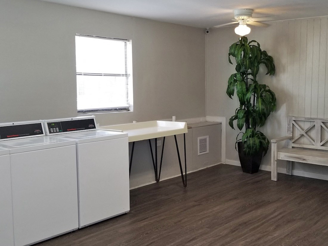 Laundry room with folding table and bench at River Road Terrace