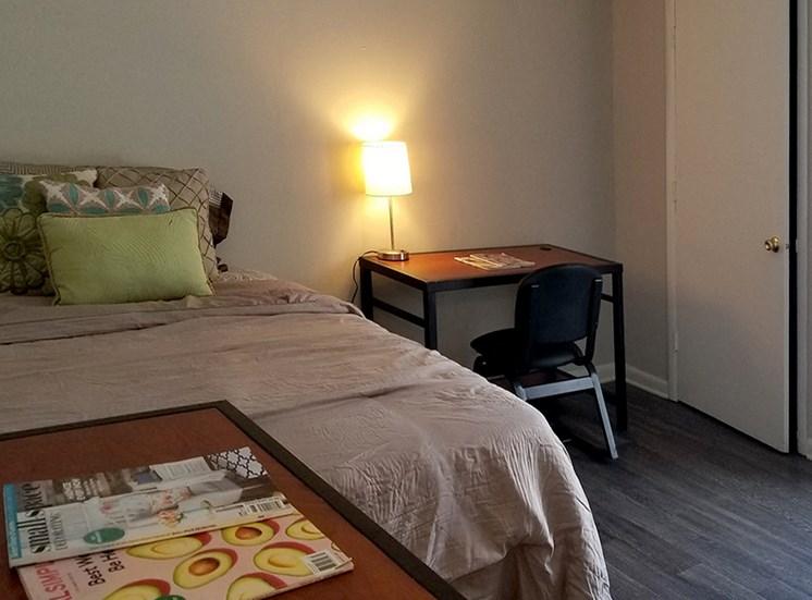 furnished bedroom with desk, bed, and dresser