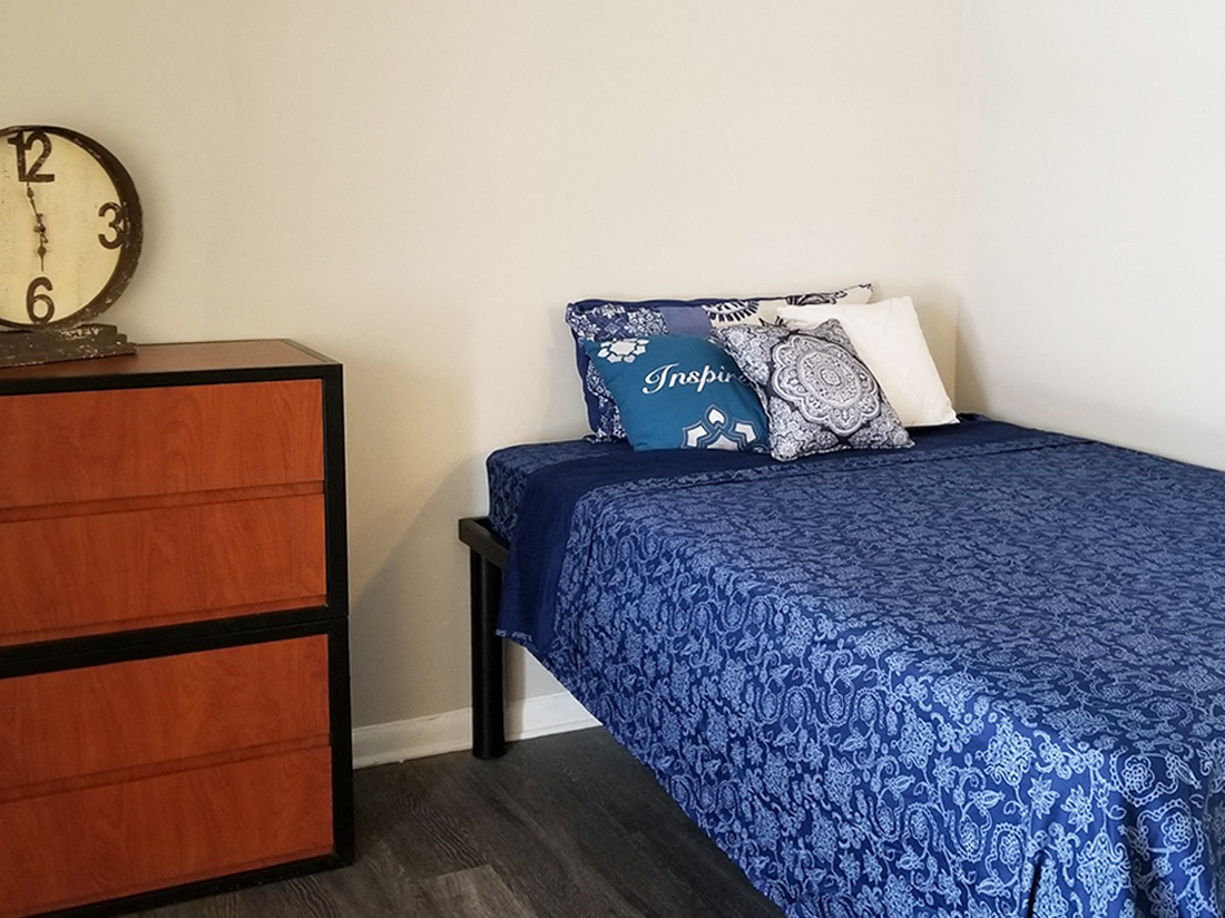 furnished bedroom with bed and side table