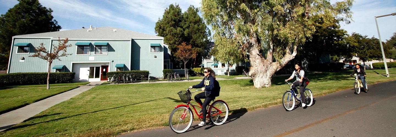 Student biking on the green belt near The Atriums