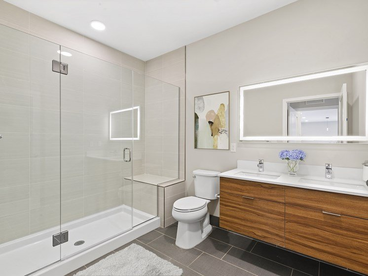 Luxurious bathroom in boutique apartment for rent with couple's vanity featuring two sinks and lighted mirror